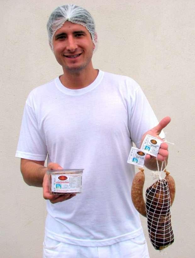 """Legenda: A empresa de produtos suínos Dagostin, de Caravaggio, vende seus ótimos produtos coma marca """"Dagosto"""" na Coofanove, Mercado Dagostin e na própria empresa. Além das carnes, há salame tipo colonial, tipo italiano, torresmo pururuca, e também está produzindo um lombo defumado que é o melhor da região. Fones: (48)9984-8758. Na foto o jovem Guilherme Dagostin com alguns produtos """"Dagosto""""."""