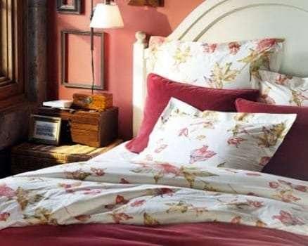 O rosa na parede é um tom de pêssego, combinado com a roupa de cama branca, com motivos florais e carmim, num tom de vermelho mais pesado, a ambientação se tornou extremamente adulta e agradável.