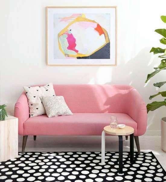 O rosa com um pigmento mais avermelhado foi utilizado no sofá, se tornando um elemento mais marcante, porém, novamente a base branca e os elementos naturais vieram suavizá-lo. Lembrando sempre que o tecido que reveste o sofá pode ser substituído quando a cor se tornar cansativa.