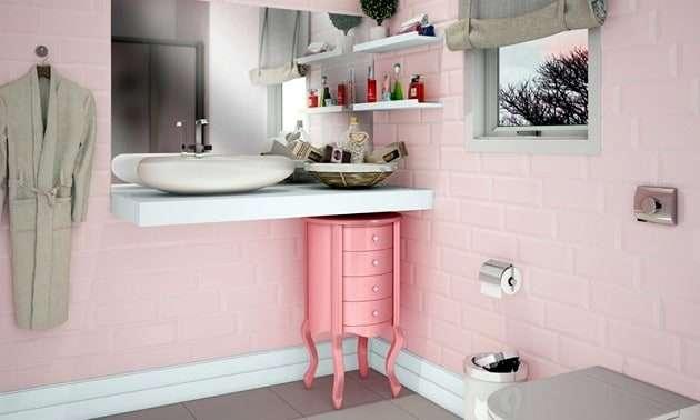 Para quem deseja um banheiro com ares de princesa, este aqui é um exemplo perfeito a se seguir. Com um revestimento rose quartz, ele é harmonizado com o branco e as tonalidades de nude da cortina e do roupão. Observa-se que essa ambientação já tornou o espaço mais feminino, e doce.
