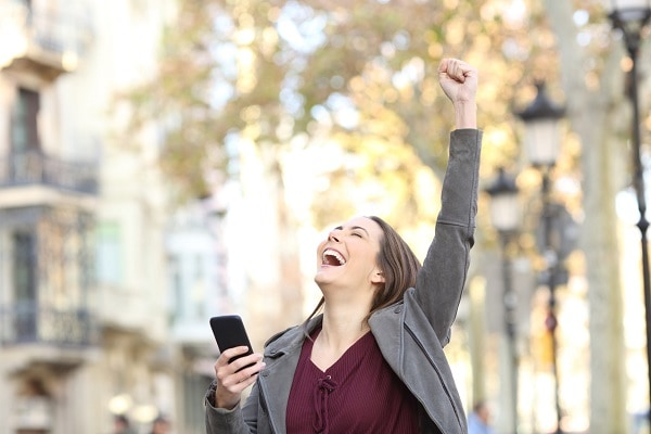 Excited woman holding phone and raising arm in the street